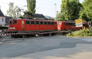 Über den Bahnübergang in der Aachener Straße donnert ein Güterzug mit zwei Lokomotiven. Die Bahnschranken sind ebenso in die Jahre gekommen wie das alte Gleisnetz am Westufer.