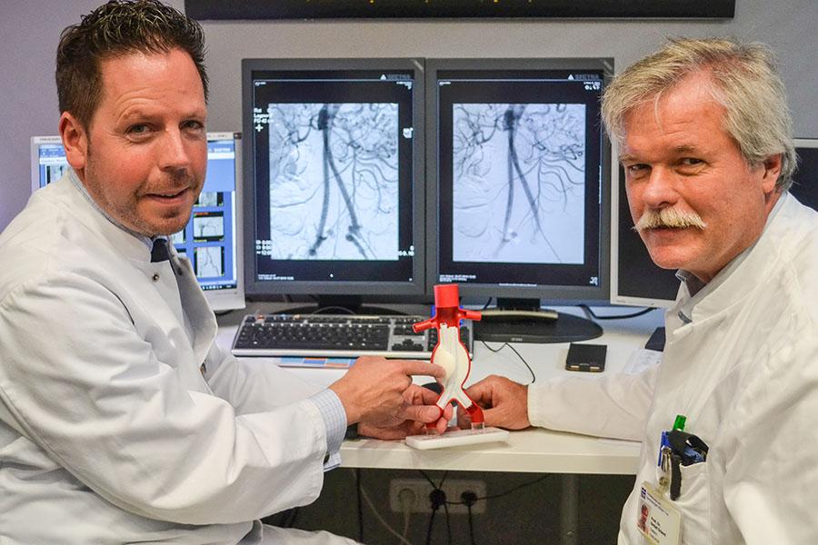Die beiden Chefärzte Professor Dr. med. Winfried A. Willinek (links) und Professor Dr. med. Detlef Ockert präsentieren das Modell einer Aortenprothese. Foto: Brüderkrankenhaus Trier