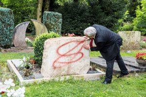 Betroffen untersucht Dezernent Andreas Ludwig einen der beschmierten Grabsteine. Foto: Rolf Lorig