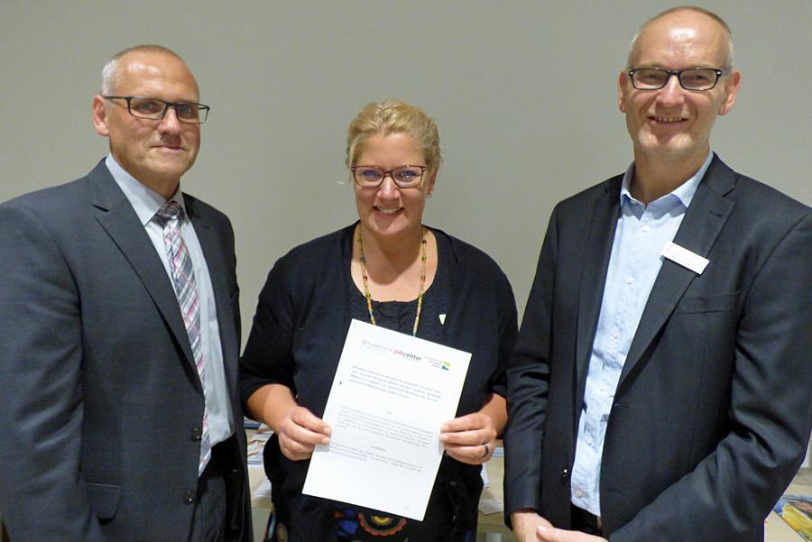 Manfred Greis (Jobcenter Bernkastel-Wittlich), Silke Meyer (Landkreis Bernkastel-Wittlich) und Christian Thömmes (Agentur für Arbeit Trier) halten die neue Kooperationsvereinbarung in Händen.