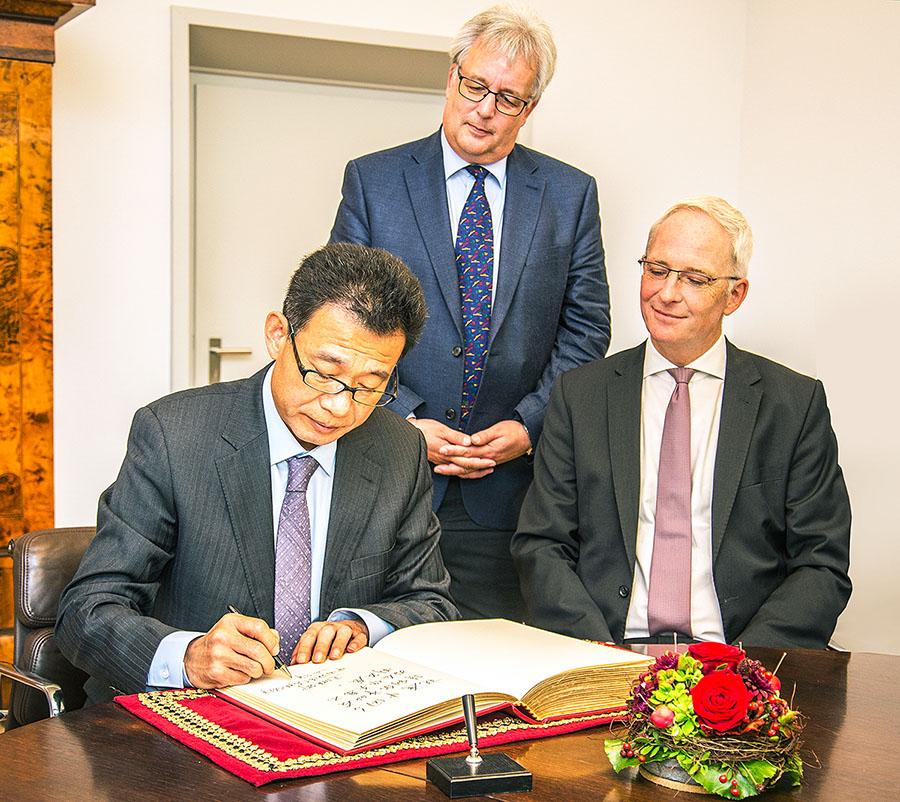 Im Beisein von Dezernent Andreas Ludwig und OB Wolfram Leibe trägt sich der Generalkonsul in das Gästebuch der Stadt Trier ein. Foto: Presseamt