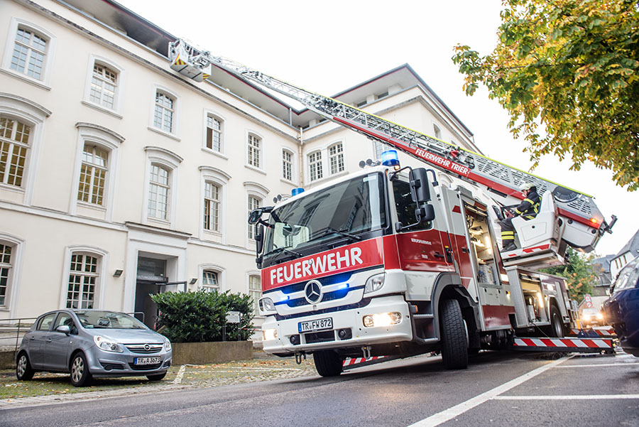 Über eine Drehleiter erreichen die Feuerwehrleute den Brandherd. Von der Straße aus sind die Rußspuren am Dach zu erkennen. Fotos: Rolf Lorig