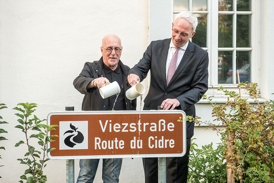 Mit ein paar Schlucken Viez taufen Haspitt Weiler (links) und Wolfram Leibe das neue Schild am Rathaus. Fotos: Rolf Lorig