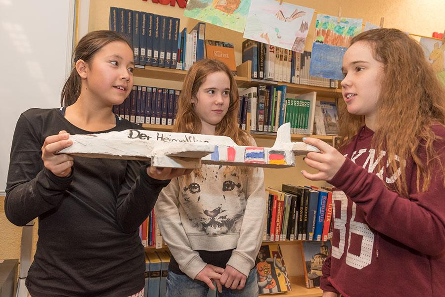 """Alina, Emily und Lisa nähern sich dem Begriff """"Heimat"""" über ein selbstgebautes Flugzeug, das die Flaggen ihrer Heimatländer trägt. Fotos: Rolf Lorig"""