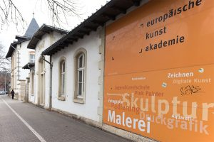 Hier arbeiten wir! Gelungener Hinweis auf die Akademie in der Aachener Straße.