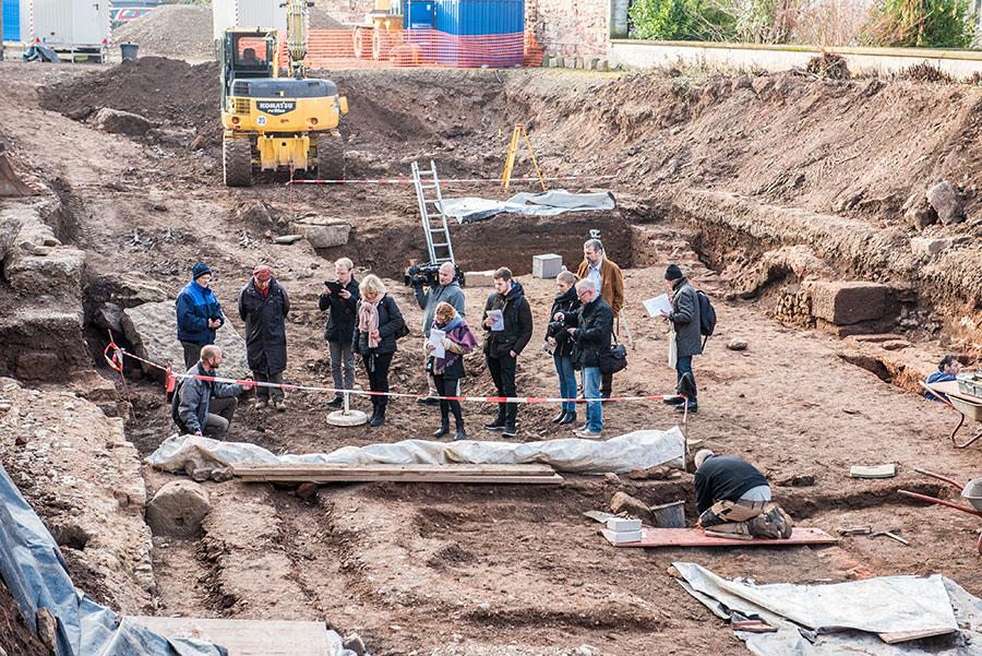 Grabungsleiter Joachim Hupe (links kniend) lerläutert den Journalisten die Bedeutung der Ausgrabung. Fotos: Rolf Lorig