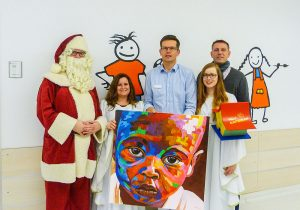 Über den Besuch des Weihnachtsmanns und seiner Engel freuen sich Chefarzt Wolfgang Thomas (Mitte) und Christoph Block vom Verein Villa Kunterbunt. Foto: Trier-Galerie