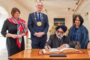 Der indische Botschafter Gurjit Singh (Mitte) trägt sich im Beisein seiner Gattin Neeru Singh (r.) und von Oberbürgermeister Wolfram Leibe (2. v. l.) und dessen Frau, Professor Andrea Sand (l.), in das Goldene Buch der Stadt ein. Foto: Rolf Lorig