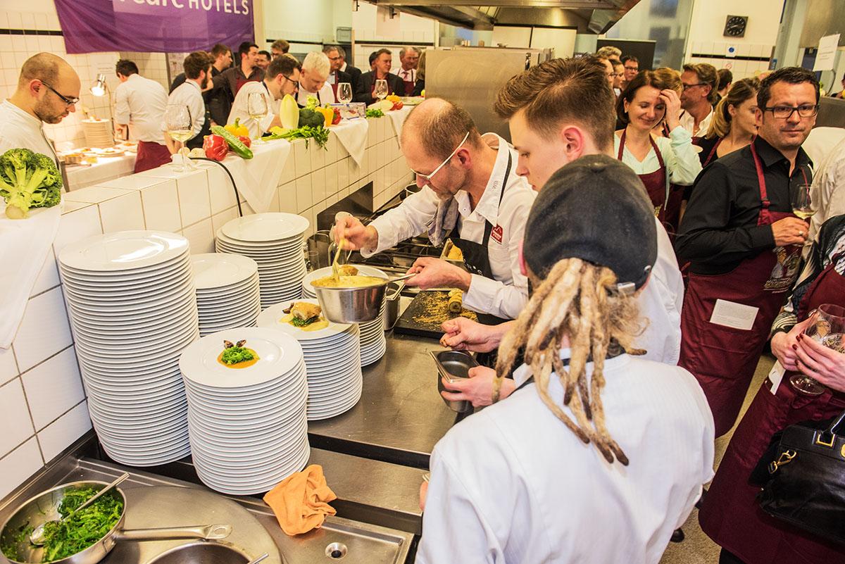 """Großer Andrang an allen Kochstationen. Bei Wolfgang Becker (vorne) gibt es """"Veggie's Delight"""". Alle Fotos: Rolf Lorig"""