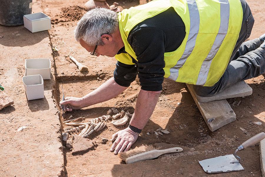 Vorsichtig legt ein Grabungshelfer das Skelett eines Kindes frei. Fotos: Rolf Lorig