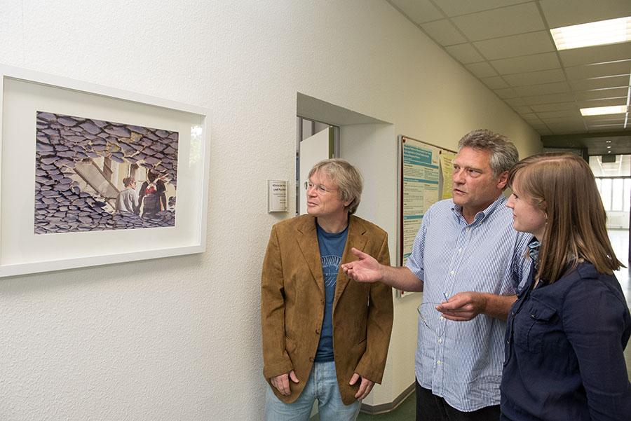 Vorbeigehende Menschen spiegeln sich in einer Pfütze: Uli Schmidt (Mitte) berichtet Wolfgang Lutz und Ann-Kathrin Schiefele von der Entstehung der Aufnahme. Foto: Rolf Lorig