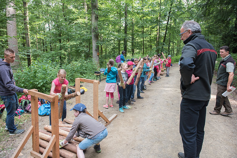 Hier geht es um Schnelligkeit und Teamfähigkeit: Forstamtleiter Gundolf Bartmann beobachtet die Kinder beim Holzstapeln. Fotos: Rolf Lorig