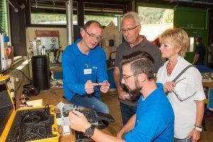 Nachrichtentechniker Paul Kall (links) und Azubi Gabriel Koch erläutern den Besuchern die Herausforderungen beim Verlegen von Glasfaserkabeln für das schnelle Internet
