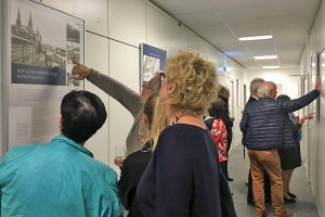 Besucher der Vernissage betrachten eines der ausgestellten Plakate. Foto: ttm