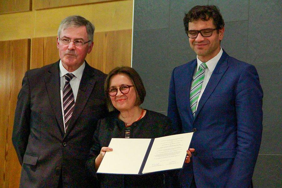Prrofessor Gernot Wilhelm (links) und Staatssekretär Salvatore Barbaro gratulieren der Preisträgerin. Foto: Hochschule Trier